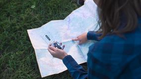 Woman Traveling, Using Map And Compass In Nature. Woman Traveling, Using Map And Compass, Searching For Road Using Travel Equipment In Nature stock video