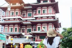 Woman traveling with white dress and hat, Asian traveler looking to Buddha Tooth Relic Temple in Chinatown of Singapore. landmark. And popular for tourist stock images