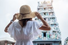 Woman traveling with white dress and hat, happy Asian traveler looking to Sri Mariamman Temple in Chinatown of Singapore. landmark. And popular for tourist stock photos