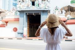 Woman traveling with white dress and hat, happy Asian traveler looking to Sri Mariamman Temple in Chinatown of Singapore. landmark. And popular for tourist royalty free stock images