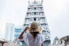 Woman traveling with white dress and hat, happy Asian traveler looking to Sri Mariamman Temple in Chinatown of Singapore. landmark. And popular for tourist stock image