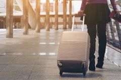 Woman traveller in airport walkway. Travel concept. Woman traveller with travel bag or luggage walking in airport terminal walkway for travel abroad stock image