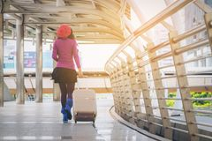 Woman traveller in airport walkway. Travel concept. Woman traveller walking in airport walkway with travel bag or luggage. Traveler travel abroad through Royalty Free Stock Photos