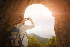 Woman traveller with backpack the photographing on the smartphon. Tourist with backpack, photographing on the smartphone sunrise from the cave Stock Photography