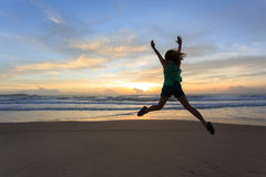 Woman traveller happy jumping on the beach with sunrise Stock Photo