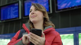 Woman holding mobile phone and looking at information board in airport. Woman traveller holding mobile phone and looking at information board in airport stock footage