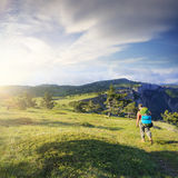 Woman traveller on mountain field Royalty Free Stock Photo