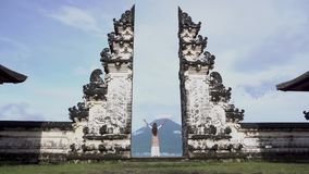 Woman raise hands standing in Pura Lempuyang, looking at Agung volcano.Indonesia