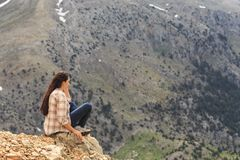 Woman traveller sitting legs crossed on edge and enjoying mounta royalty free stock photo