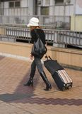 Woman travelling. Woman with travel bags walking in a city Stock Images