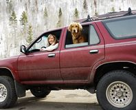 Woman travelling. Woman and dog in dirt splattered SUV looking out windows in snowy countryside Royalty Free Stock Image
