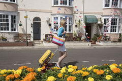 Woman travelling alone in seaside town. Female holidaymaker with a yellow suitcase looking for B&B accommodation along a street of small hotels in an English Stock Image