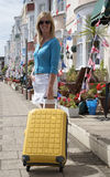 Woman travelling alone in seaside town. Holidaymaker travelling alone with suitcase looking for B&B accommodation at a seaside town in southern England UK stock photos