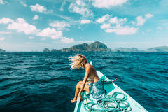 Woman travelling on the boat in Asia. Back view of the young woman relaxing on the boat and looking at the island. Travelling tour in Asia: El Nido, Palawan Stock Photos