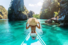 Woman travelling on the boat in Asia. Back view of the young woman in straw hat relaxing on the boat and looking forward into lagoon. Travelling tour in Asia: El Stock Image