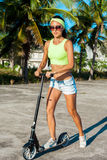 Woman travelling by scooter. Happy sexy woman kick scootering on the beach near palms in tropical country. Royalty Free Stock Photos