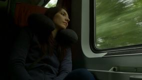 Woman Travelling by Train. Woman is travelling by train and has an inflatable travel pillow around her neck stock footage
