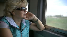 Woman travelling by train and looking out of window, dress glasses stock footage