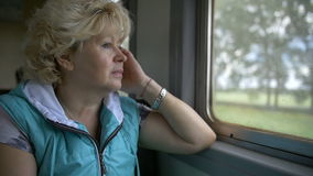 Woman travelling by train and looking out of window, slow motion. Woman travelling by train and looking out of window, have fun stock video footage