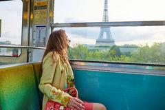 Woman travelling in a train of Parisian underground. Beautiful young woman travelling in a train of Parisian underground and looking through the window at the Stock Photo