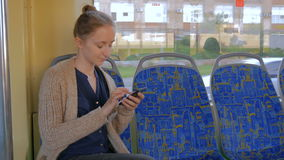 Woman travelling by tram and using smartphone. Travel, transport and technology concept stock video footage