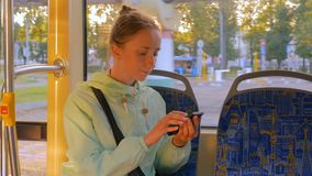 Woman travelling by tram and using smartphone. Travel, transport and technology concept stock footage