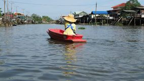 A woman travels by boat on a canal near Bangkok stock footage