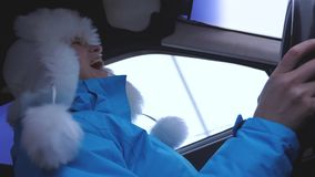 Woman travels in her car in winter, listens to music and dances. A woman drives a car in the winter snowy season. Independent and free women. girl driving a stock video