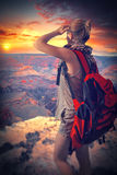 Woman travels to the Grand Canyon. With a backpack. enjoying the sunset Royalty Free Stock Photo