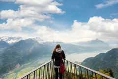 Woman traverler looking aerial view of the city district and Interlaken from viewpoint at Harder Kulm in Bern, Switzerland. Stock Image