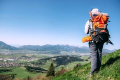Woman traweler with backpack stay on the top of hill Stock Photo