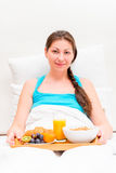 Woman with a tray of breakfast in bed in the morning Stock Image