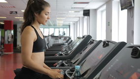 The woman on the treadmill performs the adjustment and starts to step. stock footage