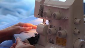 Woman treated tissue using overlock. Cuts the fabric edge. Women's hands. Quickly sew close-up. stock footage