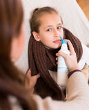 Woman treating daughter for rhinitis Stock Photo
