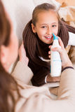 Woman treating daughter for rhinitis Royalty Free Stock Photo