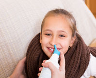 Woman treating daughter for rhinitis Stock Images
