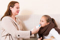 Woman treating daughter for rhinitis Royalty Free Stock Photography