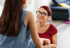 Woman Treating Scratch On Her Daughter Leg At Home. Hispanic mom treating daughter injury on knee. Family life at home with latina women helping and taking care Royalty Free Stock Photography
