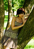 Woman with Tree. Young beautiful woman standing near the tree in the park Stock Photos