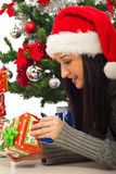 Woman and tree opening Xmas gift Royalty Free Stock Photo