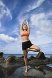 Woman in tree pose. Asian woman on rock by ocean in Maui, Hawaii doing standing tree yoga pose royalty free stock photo