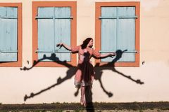 Woman with a tree shadow on the wall. Beautiful woman with the shadow of a pollarded plane tree on the wall Royalty Free Stock Images