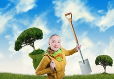 Woman with tree and spade. Smiling happy young woman with tree and spade; green meadow and blue sky as a background Royalty Free Stock Photography