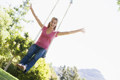 Woman on tree swing smiling Stock Photo