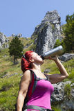 Woman trekker drinking whilst resting high in the mountains Stock Photos