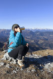 Woman trekker drinks in mountains Stock Image