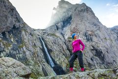 Woman trekker is standing against high mountains waterfall in Ca Royalty Free Stock Photography