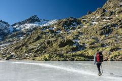 Gredos, Spain. 12-January-2019. Woman trekker walking above beautiful frozen lake during a sunny winter day stock photography