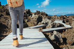 Woman trekker walking on wooden board path. Closeup photo of woman trekker walking on wooden board path ready to viewing beautiful natural landscape at summer Stock Image